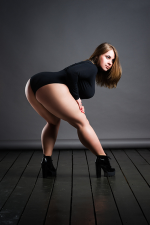 Plus size sexy model in black bodysuit, fat woman on gray studio background, overweight female body, full length portrait