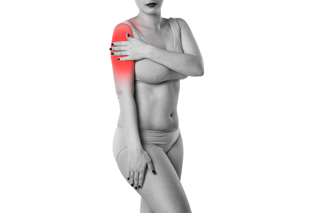 Woman with pain in shoulder isolated on white background, studio shot with red dot
