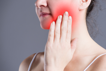 Woman with toothache, teeth pain closeup on gray background