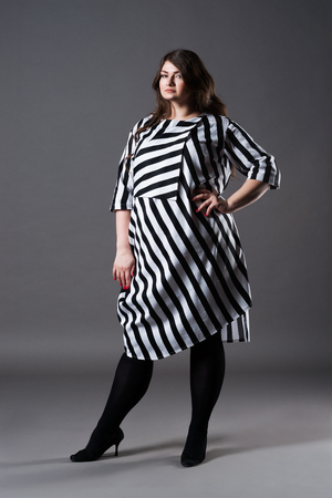 Plus size fashion model in striped dress, fat woman on gray studio background, overweight female body, full length portrait