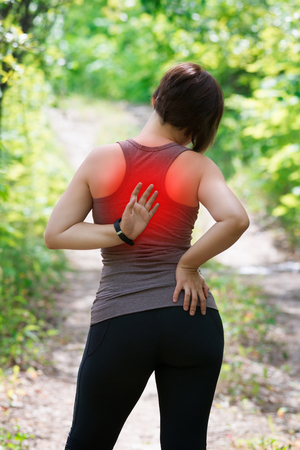 Woman with back pain, injury while running, trauma during workout, outdoors concept
