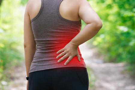 Mujer con dolor de espalda, inflamación de los riñones, lesiones durante el entrenamiento, concepto al aire libre