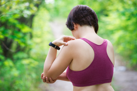 Woman with pain in hand, shoulder injury, trauma during workout, outdoors concept Фото со стока