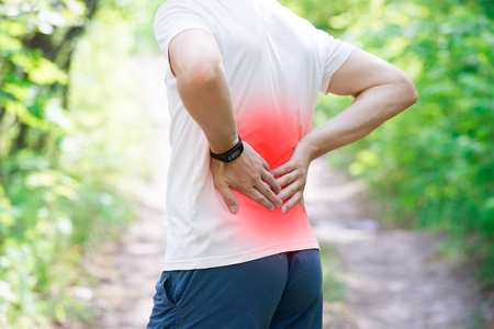 Man with back pain, injury while running, trauma during workout, outdoors concept 写真素材