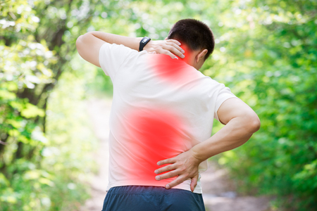 Man with back pain, injury while running, trauma during workout, outdoors concept Stock Photo