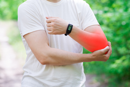 Man with pain in hand, injury while running, trauma during workout, outdoors concept Фото со стока