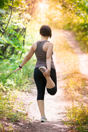 Woman warming up before jogging, outdoor exercise, healthy lifestyle concept Stock Photo
