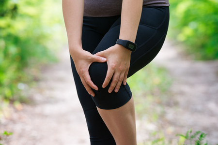Pain in woman's knee, massage of female leg, injury while running, trauma during workout, outdoors concept Stock Photo