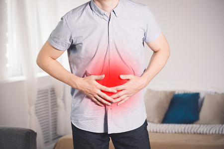 Stomach ache, man with abdominal pain suffering at home, painful area highlighted in red