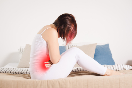 Stomach ache, woman with abdominal pain suffering at home, painful area highlighted in red
