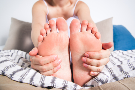 Woman's leg hurts, pain in the foot, massage of female feet at home Stock Photo