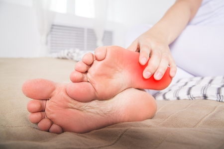 Woman's leg hurts, pain in the heel, massage of female feet at home