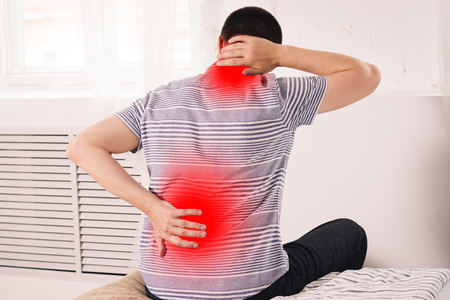 Neck pain, man suffering from backache at home, painful area highlighted in red