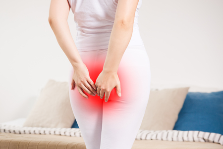 Woman suffering from hemorrhoids at home, anal pain, painful area highlighted in red