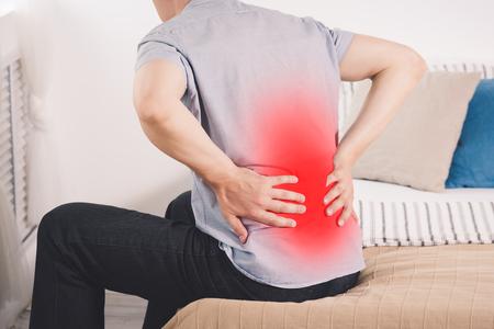 Dolor de espalda, inflamación de los riñones, hombre que sufre de dolor de espalda en casa, área dolorosa resaltada en rojo Foto de archivo