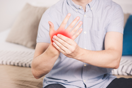 Pain in hand, man suffering from carpal tunnel syndrome at home, painful area highlighted in red