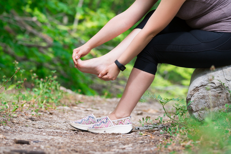 Pain in woman's foot, massage of female leg, injury while running, trauma during workout, outdoors concept 版權商用圖片