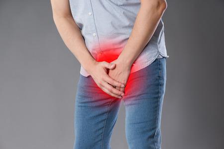 Dolor en la próstata, hombre que sufre de prostatitis o de una enfermedad venérea, foto de estudio sobre fondo gris, área dolorosa resaltada en rojo Foto de archivo