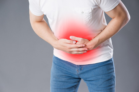 Man with abdominal pain, stomach ache on gray background, painful area highlighted in red