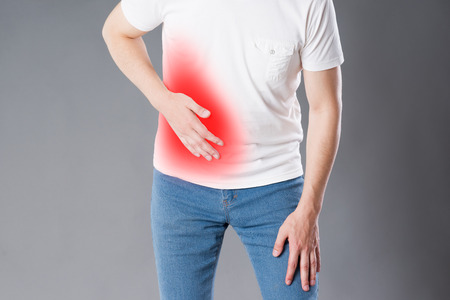 Attack of appendicitis, man suffering with abdominal pain on gray background, painful area highlighted in red