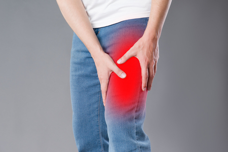 Man with pain in knee, studio shot on gray background, painful area highlighted in red