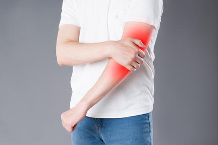 Hombre que sufre de dolor en el codo, inflamación de las articulaciones, área dolorosa resaltada en rojo