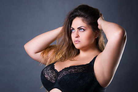 Plus size sexy model in black bra, fat woman with big natural breast on gray studio background, overweight female body, long hair and make-up