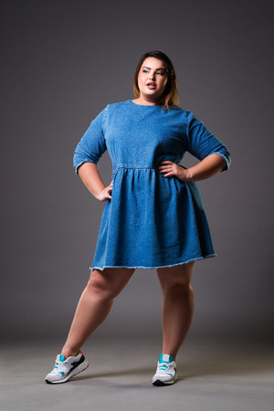 Plus size model in denim dress, fat woman on gray studio background, overweight female body, full length portrait Stock Photo