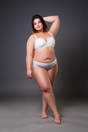 Plus size model in lingerie, fat woman on gray studio background, overweight female body, full length portrait