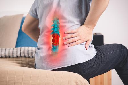 Pijn in de wervelkolom, een man met rugpijn thuis, letsel in de onderrug, foto met gemarkeerd skelet