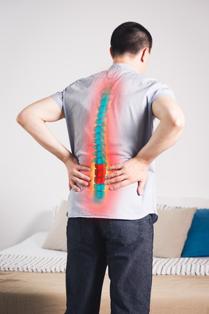 Pain in the spine, a man with backache at home, injury in the lower back, photo with highlighted skeleton