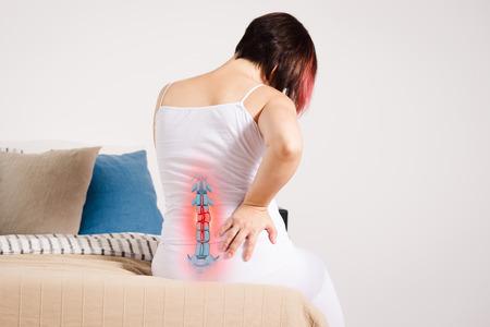Dolor en la columna, mujer con dolor de espalda en casa, lesión en la espalda baja, foto con esqueleto resaltado Foto de archivo
