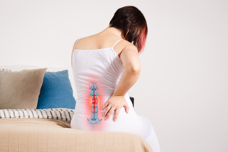 Pain in the spine, woman with backache at home, injury in the lower back, photo with highlighted skeleton Stockfoto - 110896260