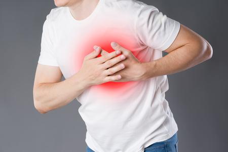 Zawał serca, mężczyzna z bólem w klatce piersiowej na szarym tle z czerwoną kropką