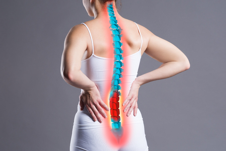 Pain in the spine, woman with backache on gray background, back injury, photo with highlighted skeleton Foto de archivo