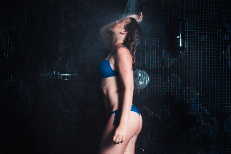 Young woman in blue bikini taking a shower, water treatment and body care concept
