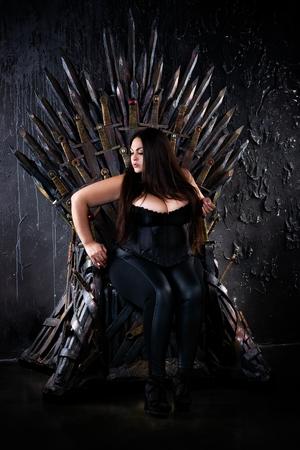 Plus size fashion model sitting on the iron throne, sexy woman in gothic interior