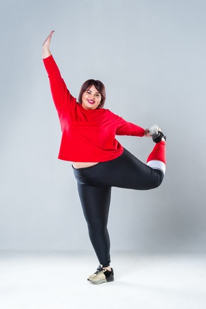 Plus size model in sportswear, fat woman doing workout on gray background, overweight female body, healthy lifestyle concept Stock Photo