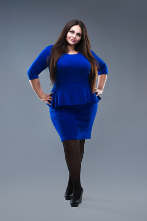 Plus size fashion model in blue dress, fat woman on gray studio background, overweight female body, full length portrait