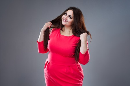 Happy plus size fashion model in red dress, fat woman on gray studio background