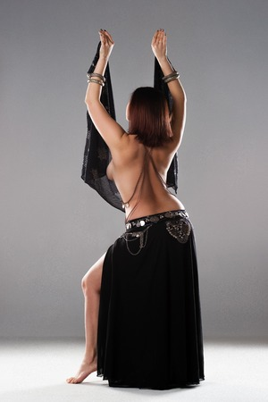 Sexy women performs belly dance in ethnic dress on gray background, studio shot Standard-Bild