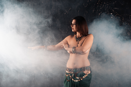 Sexy women performs belly dance in ethnic dress on dark smoky background, studio shot