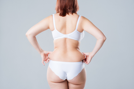 Overweight woman with fat back and buttocks, obesity female body on gray background, studio shot