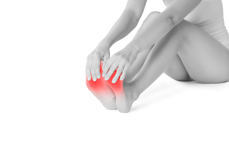 Pain in womans legs, massage of female feet isolated on white background, painful area highlighted in red