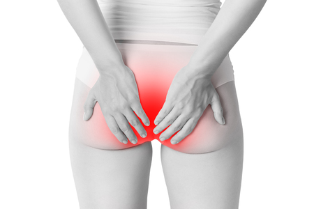 Woman suffering from hemorrhoids, anal pain isolated on white background, painful area highlighted in red Imagens