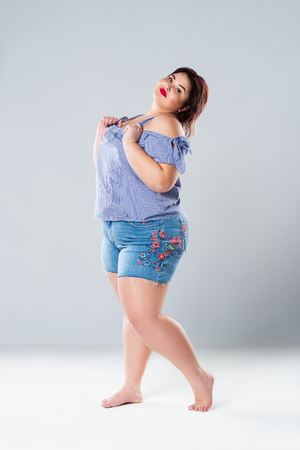 Plus size fashion model in jean shorts, fat woman on gray studio background, overweight female body