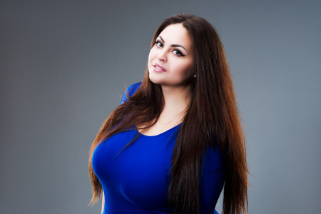 Brunette plus size fashion model in blue dress, fat woman with long hair on gray background, studio shot Stockfoto