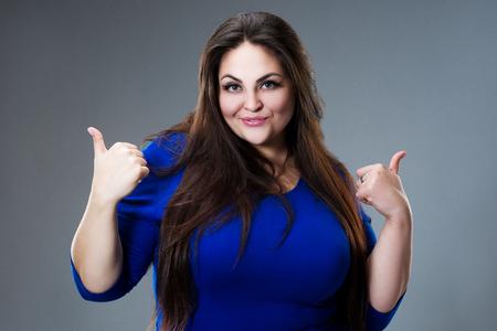 Happy plus size fashion model in blue dress, sexy fat woman on gray studio background