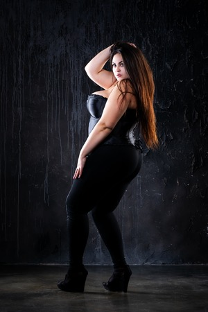 Plus size fashion model in sexy clothes, fat woman on black background, body positive concept, full length portrait 写真素材