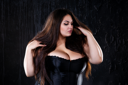Sexy plus size model in black corset, fat woman with big natural breasts on dark background, body positive concept, studio shot 免版税图像